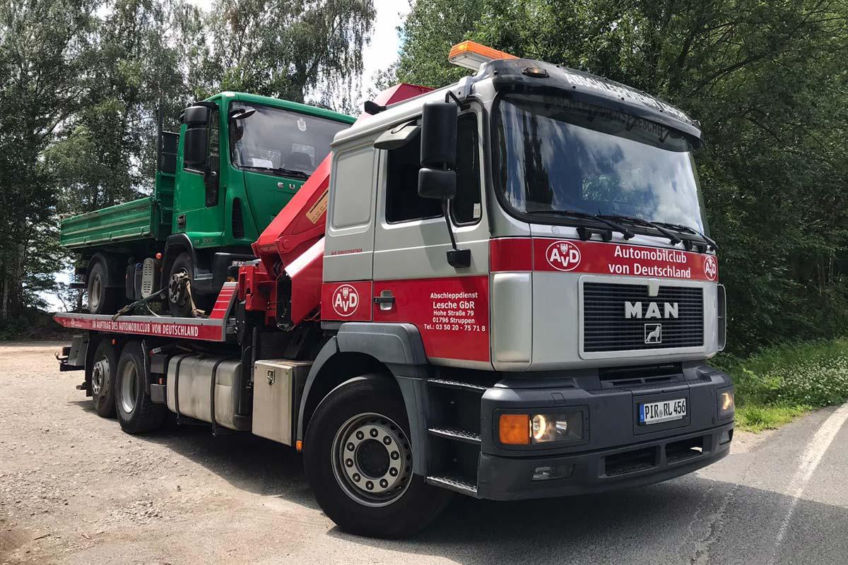 3-Achs Plateaufahrzeug mit Kran MAN schleppt LKW ab