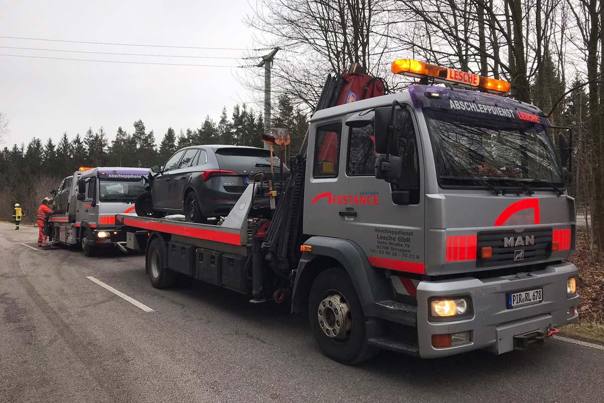 Abschleppen eines Unfallwagens mit Plateaufahrzeug mit Kran