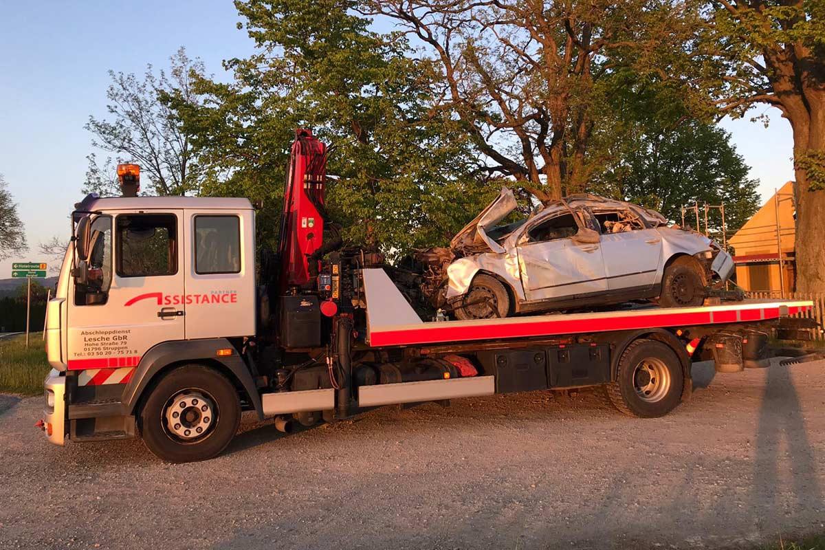 Plateaufahrzeug mit Kran schleppt Fahrzeug mit Totalschaden ab