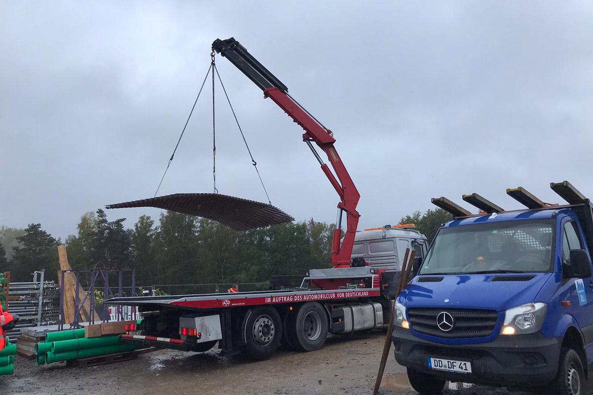 Transport von Gitterplatten mit 3-Achs Plateaufahrzeug mit Kran